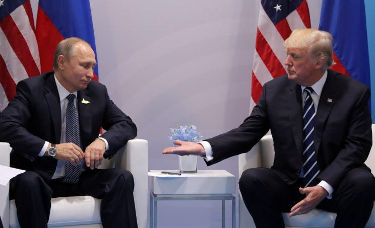 Trump extends his hand to Putin at the G-20 summit in Hamburg, Germany, on Friday. (Carlos Barria/Reuters)