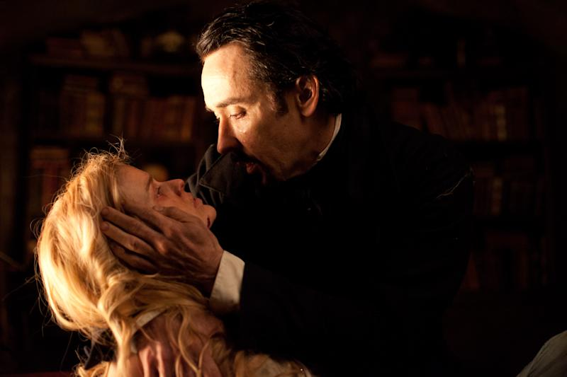 """In this film publicity image released by Relativity Media, John Cusack portrays Edgar Allan Poe, right, and Alice Eve portrays Emily Hamilton in a scene from the gothic thriller """"The Raven."""" (AP Photo/Relativity Media, Larry Horricks)"""