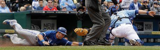 Toronto Blue Jays' J.P. Arencibia, left, beats the tag by Kansas City Royals catcher Humberto Quintero, right, to score on single by Jose Bautista during the fifth inning of a baseball game on Sunday, April 22, 2012, in Kansas City, Mo. (AP Photo/Charlie Riedel)