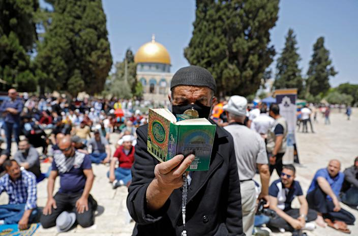 A man reads the holy Quran as Palestinians gather during the second Friday prayers of the Islamic fasting month of Ramadan, outside the Dome of the Rock at the Al-Aqsa Mosque compound, Islam's third holiest site, in Jerusalem's Old City, on April 23, 2021.