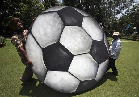 Labourers carry a plywood cut-out of a soccer ball in Chandigarh