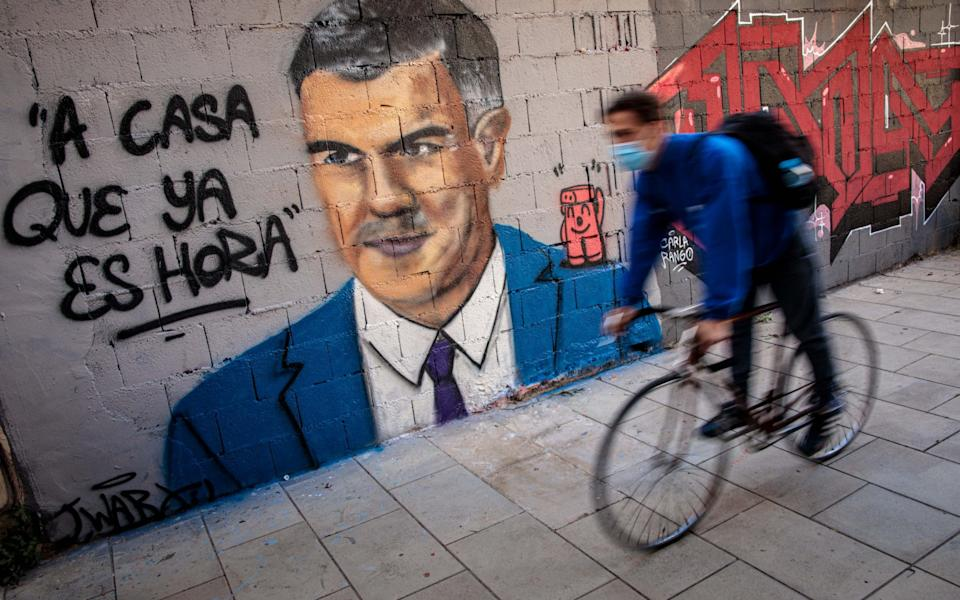A man rides a bicycle a mural depicting Spanish Prime Minister Pedro Sanchez and a phrase reading 'Time to go home'