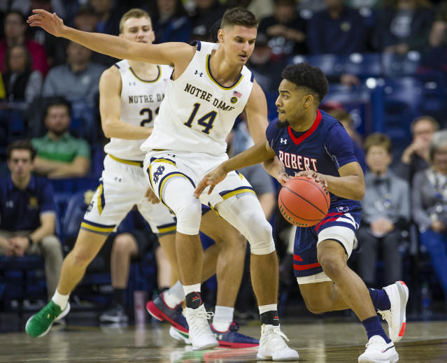 Robert Morris' Sayveon McEwen (12) tries to get past Notre Dame's Nate Laszewski (14) during an NCAA college basketball game Saturday, Nov. 9, 2019 at Purcell Pavilion in South Bend, Ind. (Michael Caterina/South Bend Tribune via AP)