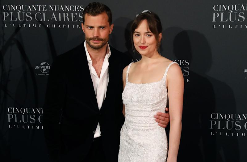 Actor Jamie Dornan (L) and actress Dakota Johnson pose as they arrive to attend 'Fifty Shades Freed - 50 Nuances Plus Claires' Premiere at Salle Pleyel in Paris on February 6, 2018. / AFP PHOTO / PATRICK KOVARIK (Photo credit should read PATRICK KOVARIK/AFP/Getty Images)