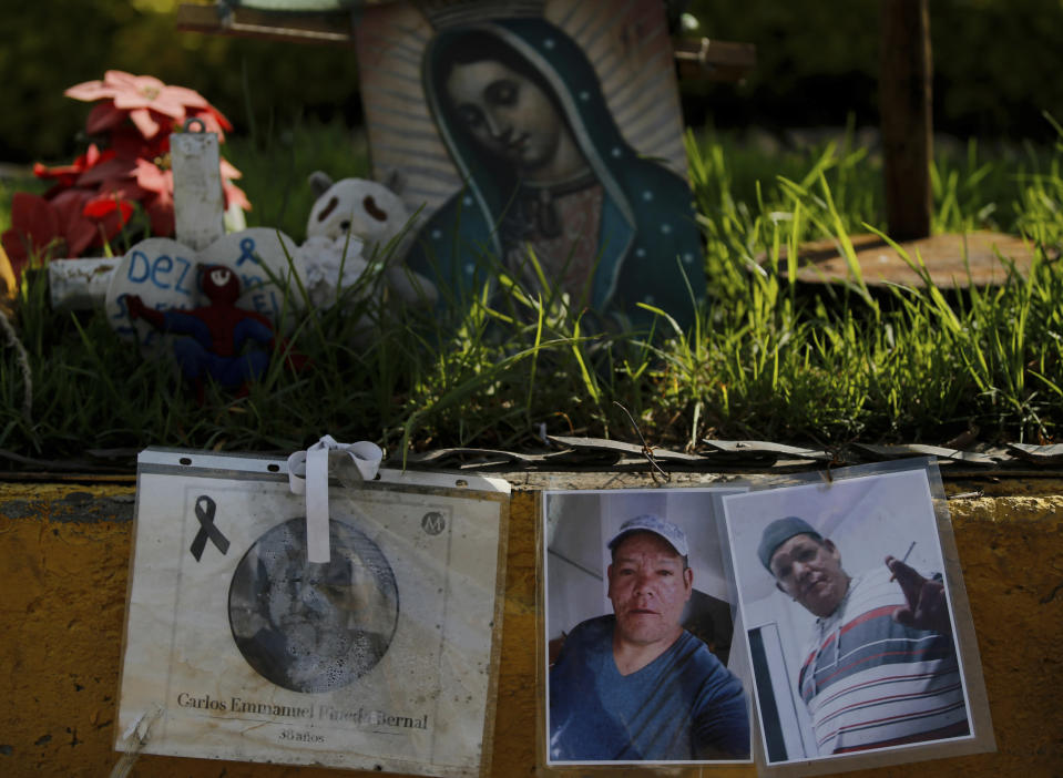 Photos of people who died in a metro collapse hang at the site of the now missing section in Mexico City, Wednesday, June 16, 2021. A June 16, 2021 preliminary report by experts into the collapse that killed 26 people placed much of the blame on poor welds in studs that joined steel support beams to a concrete layer supporting the trackbed. (AP Photo/Fernando Llano)