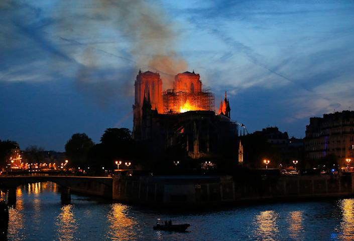 Firefighters tackle the blaze as flames and smoke rise from Notre Dame cathedral as it burns in Paris, Monday, April 15, 2019. Massive plumes of yellow brown smoke is filling the air above Notre Dame Cathedral and ash is falling on tourists and others around the island that marks the center of Paris. (Photo: Michel Euler/AP)