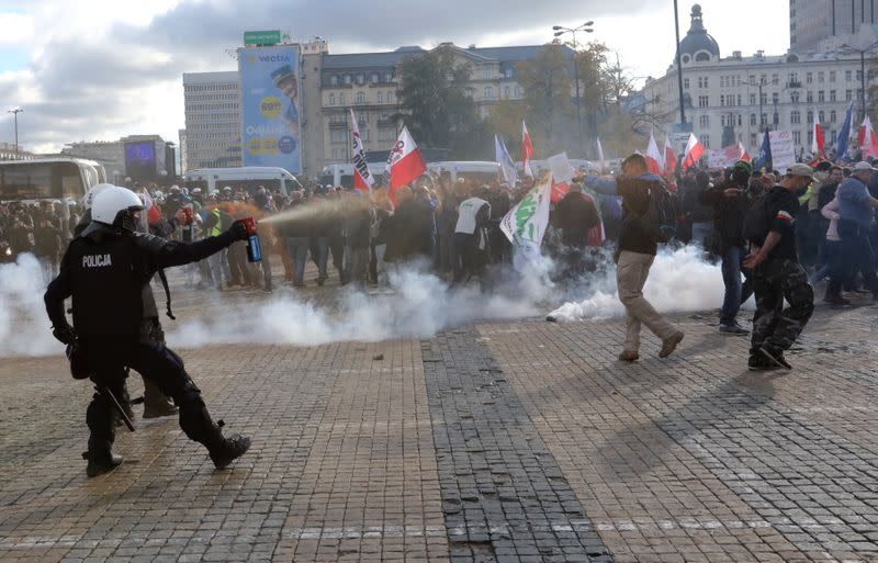 A policeman sprays demonstrators with tear gas during anti lockdown protest in Warsaw