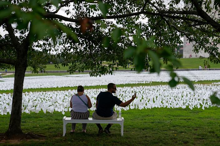 """People visit artist Suzanne Brennan Firstenberg's """"In America: Remember,"""" a temporary art installation made up of white flags to commemorate Americans who have died of COVID-19, on the National Mall in Washington, Tuesday, Sept. 21, 2021."""