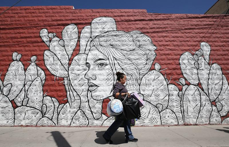 A woman walks past one of many murals in the Segundo Barrio of El Paso Sept., 12, 2019. The neighborhood is a mixed-use residential and commercial neighborhood in south El Paso.