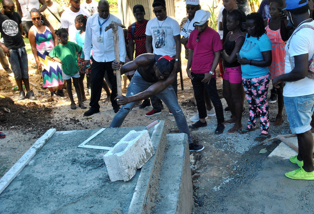 Jamaica's Olympic champion Usain Bolt (C) digs the grave for high jump star Germaine Mason, who died on April 20 in a motorbike crash on the outskirts of Kingston, in Grange Hill, Portland, Jamaica May 13, 2017. Picture taken May 13, 2017. REUTERS/Everard Owen     TPX IMAGES OF THE DAY