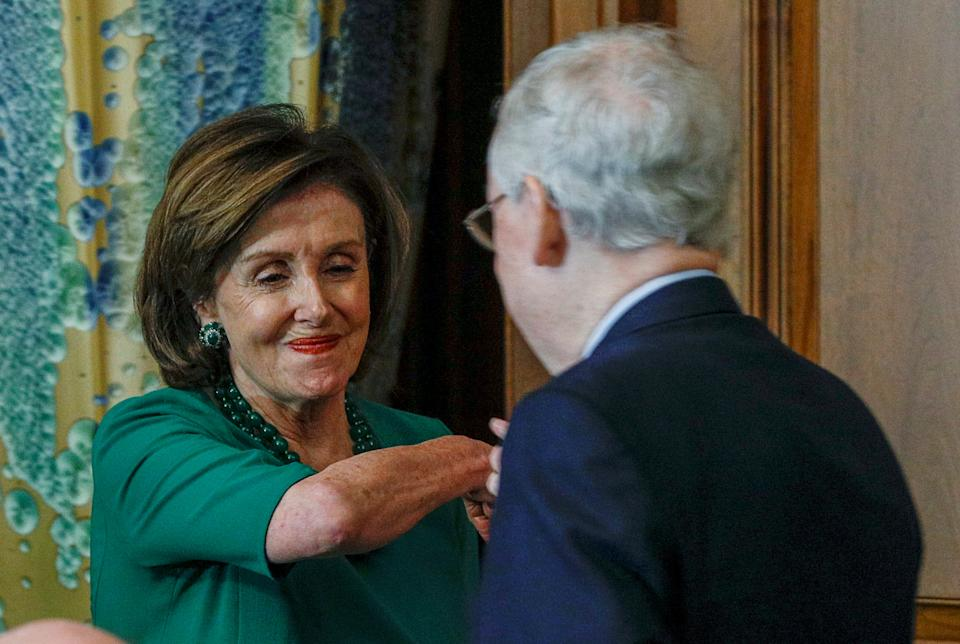 U.S. House Speaker Nancy Pelosi (D-CA) elbow bumps Senate Majority Leader Mitch McConnell (R-KY) at a Friends of Ireland luncheon on Capitol Hill in Washington, U.S., March 12, 2020. REUTERS/Tom Brenner