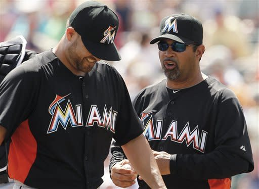 Miami Marlins starting pitcher Ricky Nolasco, left, smiles after being pulled by manager Ozzie Guillen, right, in the fifth inning of a spring training baseball game against the Atlanta Braves in Kissimmee, Fla., Thursday, March 22, 2012. (AP Photo/Paul Sancya)