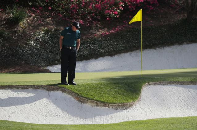 Phil Mickelson of the U.S. looks over his ball after hitting to the edge of a sand trap on the 12th hole during first round play of the 2018 Masters golf tournament at the Augusta National Golf Club in Augusta, Georgia, U.S., April 5, 2018. REUTERS/Brian Snyder