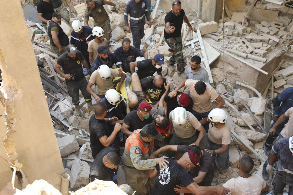 A survivor is taken out of the rubble after a massive explosion in Beirut, Lebanon, Wednesday, Aug. 5, 2020. The explosion flattened much of a port and damaged buildings across Beirut, sending a giant mushroom cloud into the sky. In addition to those who died, more than 3,000 other people were injured, with bodies buried in the rubble, officials said.(AP Photo/Hassan Ammar)