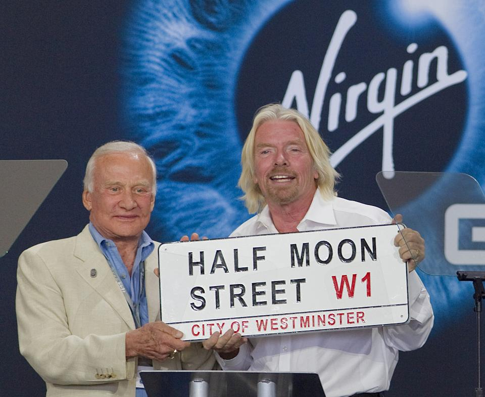 Edwin 'Buzz' Aldrin presents Richard Branson with a street sign for the road leading into Spaceport America named after Branson's companies' address in England.