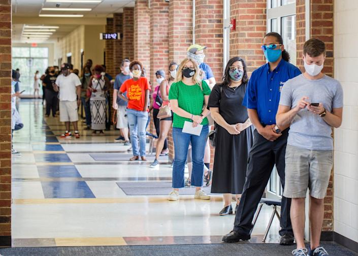 Voters wait in long lines at Peachcrest Elementary School to vote in the state's primary election on June 9, 2020, in Decatur, Ga. Coronavirus restrictions only allowed 10 people in the gym at a time so many machines were not being used, creating long wait times.