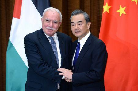 Chinese Foreign Minister Wang Yi shakes hands with his Palestinian counterpart Riyad Al-Maliki ahead of their meeting at the Ministry of Foreign Affairs in Beijing, China
