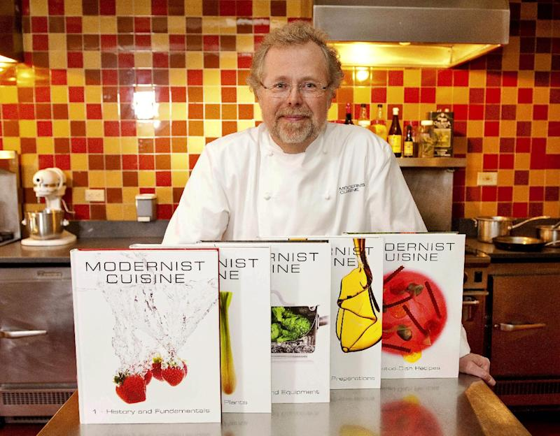 "FILE - This March 23, 2011 file photo shows Nathan Myhrvold, author of ""Modernist Cuisine: The Art and Science of Cooking,"" as he poses with books at the Institute for Culinary Education in New York. The former chief technology officer for Microsoft who turned his techie smarts to cooking in last year's massive six-volume tome ""Modernist Cuisine,"" now is turning his attention to using science in the home kitchen.  (AP Photo/Stephen Chernin, File)"