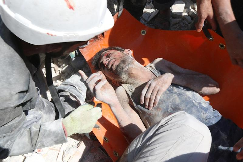 Syrian civil defence workers rescue a man from under the rubble of a building following a reported barrel-bomb attack by Syrian government forces on August 11, 2014 in the Bab al-Neirab neighbourhood of the northern city of Aleppo
