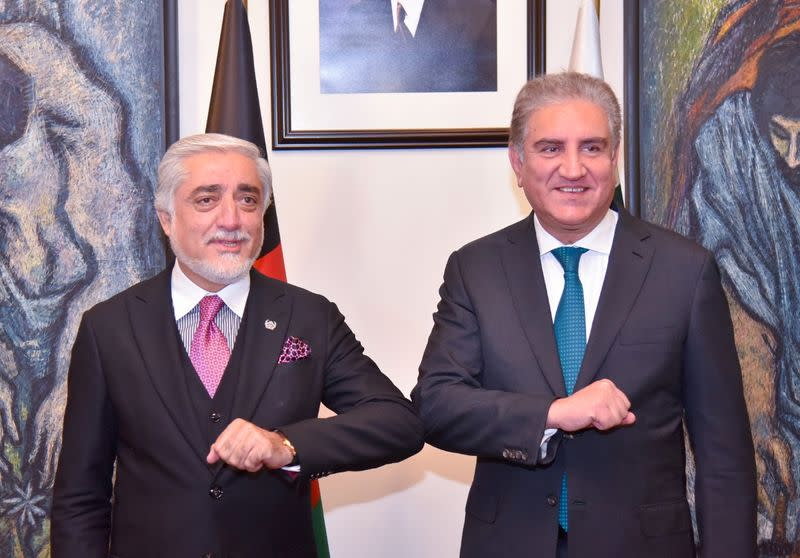 Pakistan's Foreign Minister Shah Mahmood Qureshi bumps elbows with the head of the Afghanistan's peace council, Abdullah Abdullah, upon his arrival at the Ministry of Foreign Affairs (MOFA) office in Islamabad