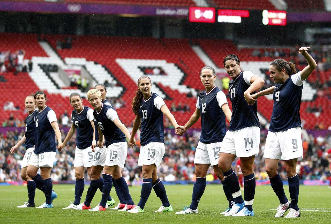 United States' Abby Wambach (14) celebrates with teammates after scoring against North Korea during their group G women's soccer match at the London 2012 Summer Olympics, Tuesday, July 31, 2012 at Old Trafford Stadium in Manchester, England. (AP Photo/Jon Super)
