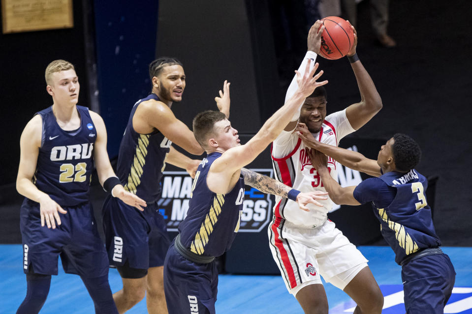 Ohio State's E.J. Liddell, second from right, gets pressure from Oral Roberts' Francis Lacis (22), Kevin Obanor, second from left, Carlos Jrgens, center, and Max Abmas (3) during the second half of a first-round game in the NCAA men's college basketball tournament, Friday, March 19, 2021, at Mackey Arena in West Lafayette, Ind. Oral Roberts won in overtime. (AP Photo/Robert Franklin)