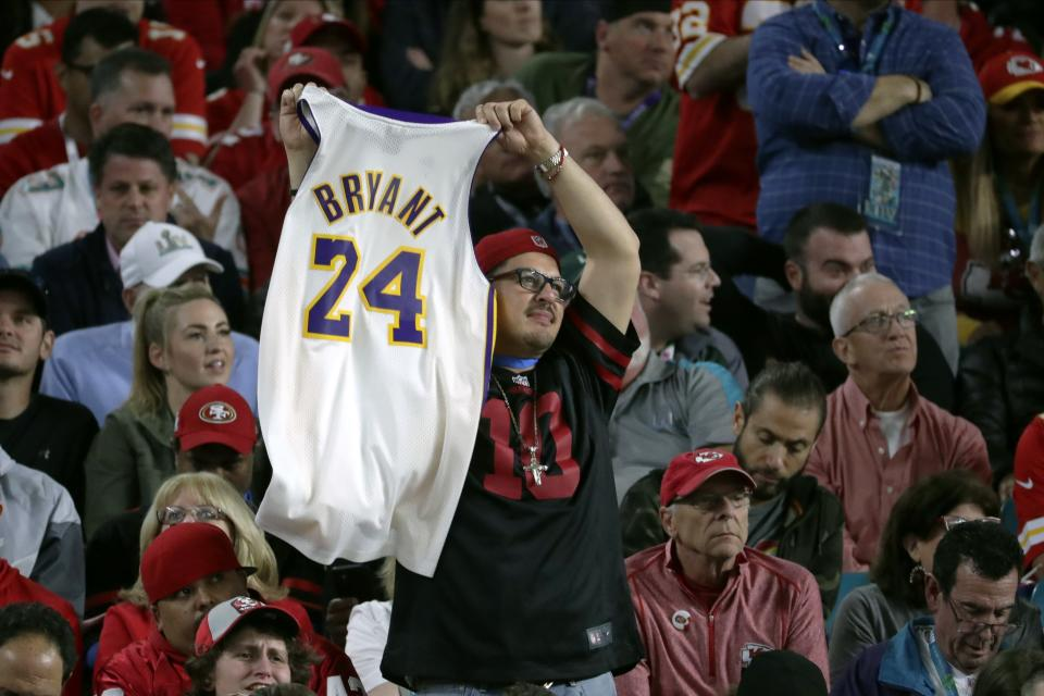 A fan in the stands holds a jersey honoring late NBA basketball legend Kobe Bryant during the second half of the NFL Super Bowl 54 football game between the San Francisco 49ers and the Kansas City Chiefs Sunday, Feb. 2, 2020, in Miami Gardens, Fla. (AP Photo/Matt York)