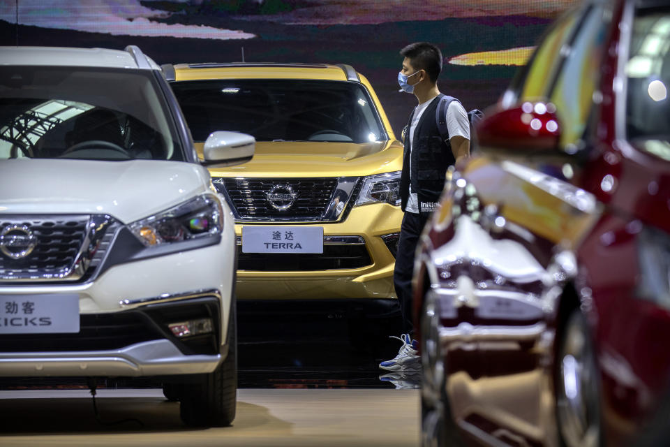 In this Sept. 26, 2020 file photo, a visitor wearing a face mask to protect against the coronavirus walks among vehicles from Nissan at the Beijing International Automotive Exhibition, also known as Auto China, in Beijing. China's sales of SUVs, minivans, and sedans fell 6% last year compared with 2019 after demand plunged due to the coronavirus and rebounded in the second half. (AP Photo/Mark Schiefelbein, File)