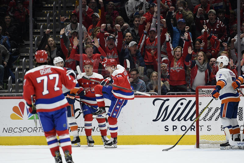 Washington Capitals center Evgeny Kuznetsov (92) celebrates his goal as New York Islanders right wing Jordan Eberle (7) looks on during the first period of an NHL hockey game, Tuesday, Dec. 31, 2019, in Washington. (AP Photo/Nick Wass)