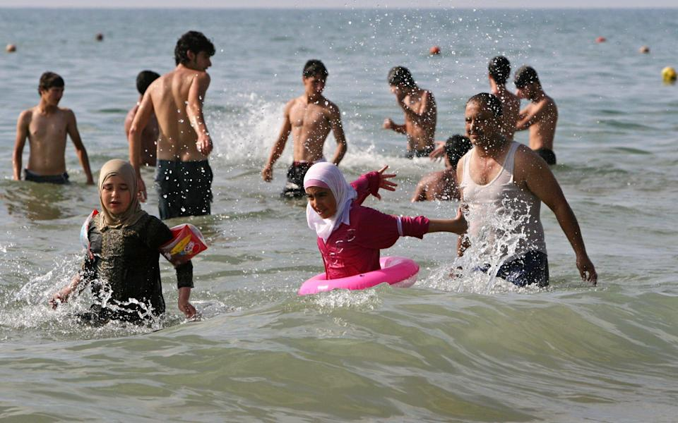 Lebanese play in the Mediterranean Sea in the southern seaport of Sidon - AP