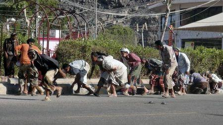 People seek shelter during a gunfire at an army base in Yemen's southern port city of Aden March 25, 2015. REUTERS/Anees Mansour