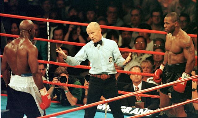 Noted boxing judge Chuck Giampa (in red tie behind referee Mills Lane) worked 135 championship fights, including the infamous 'Bite Fight' between Evander Holyfield (L) and Mike Tyson. (Getty Images)