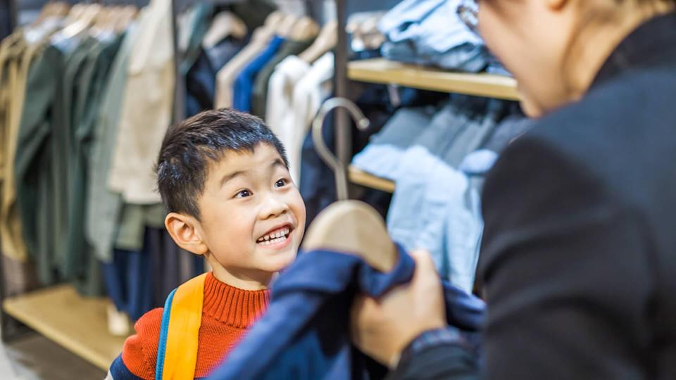 Mother and son choosing clothing indoors.