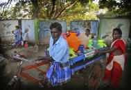 In this Monday, July 15, 2019, photo, people push a cart carrying drinking water filled from a water depot in Chennai, capital of the southern Indian state of Tamil Nadu. Rapid development and rampant construction in the coastal city of about 10 million have overtaxed a once-abundant natural water supply, forcing the government to expend huge sums to desalinate sea water, bring water by train from hundreds of miles away and deploy an army of water trucks to people whose household taps have suddenly run dry. (AP Photo/Manish Swarup)