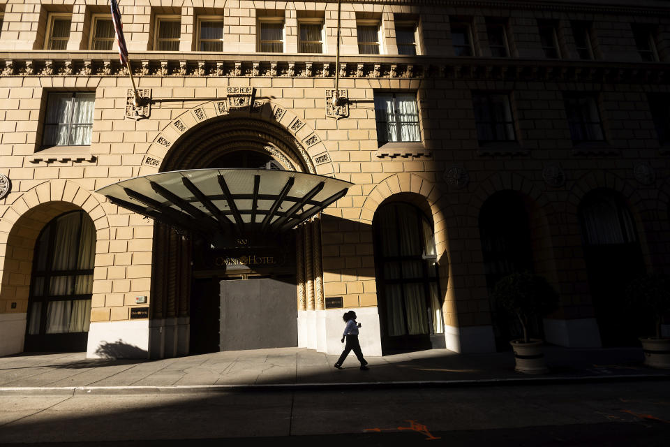 A pedestrian passes a boarded up entrance to the Omni San Francisco Hotel, which has suspended operations due to the COVID-19 pandemic, on Wednesday, Oct. 21, 2020, in San Francisco. As the coronavirus pandemic transforms San Francisco's workplace, legions of tech workers have left, able to work remotely from anywhere. Families have fled for roomy suburban homes with backyards. The exodus has pushed rents in the prohibitively expensive city to their lowest in years. (AP Photo/Noah Berger)