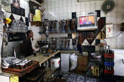 A worker at a coffee shop watches on TV as Egyptian President Mohamed Morsi takes the oath of office in Cairo on June 30. Morsi began his first full day in office on Sunday with his powers circumscribed by the military as he tries to pick a new cabinet to carry out his campaign pledges