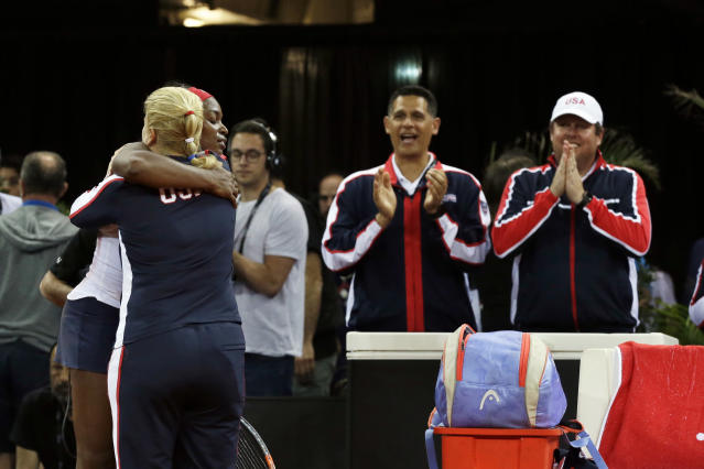 Sloane Stephens of USA celebrates with team captain Kathy Rinaldi, back to camera, after winning the Fed Cup semifinal singles tennis match against Pauline Parmentier of France, in Aix-en-Provence, southern France, Saturday, April 21, 2018. (AP Photo/Claude Paris)