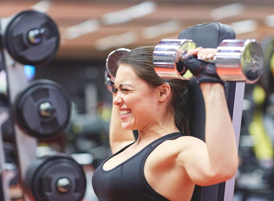 Woman straining and struggling to lift weights at gym because of lost muscle mass