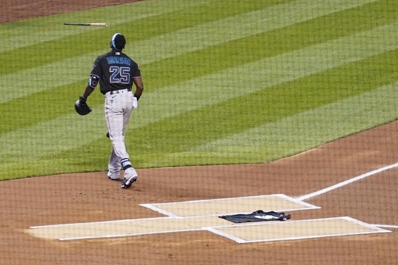 Lewis Brinson walks away after placing a Black Lives Matter shirt on home plate.