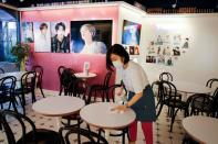 Cafe owner Kim Eun-hee, fan of K-pop boy band BTS, cleans desks with disinfectant in her cafe in Seoul