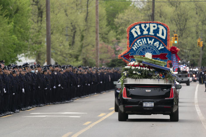 Thousands of police officers line the street as the funeral procession of New York police officer Anastasios Tsakos leaves the St. Paraskevi Greek Orthodox Shrine Church, Tuesday, May 4, 2021, in Greenlawn, N.Y. Tsakos was at the scene of an accident on the Long Island Expressway when he was struck and killed by an allegedly drunk driver a week ago. (AP Photo/Mark Lennihan)