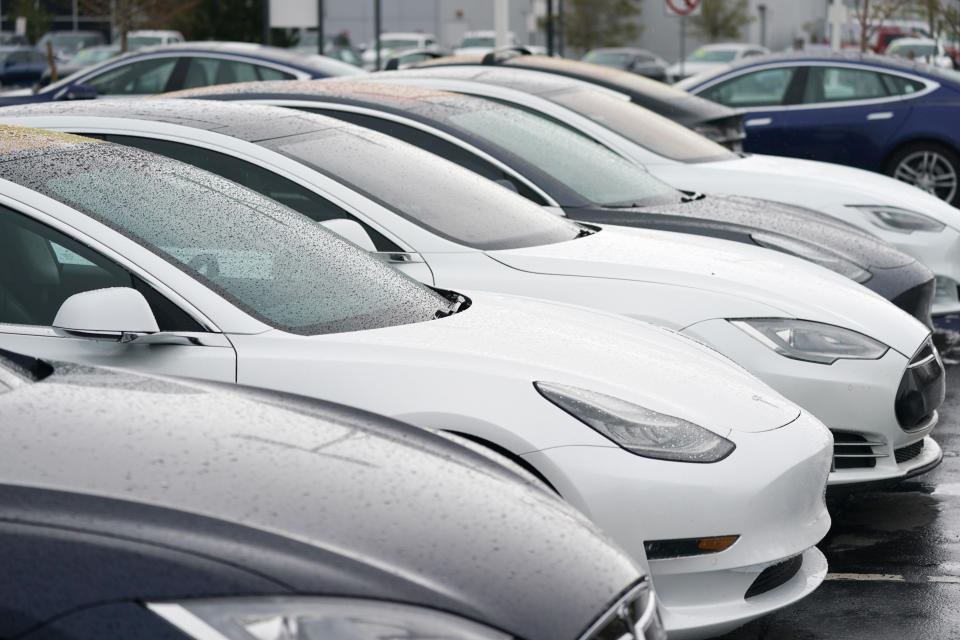 In this Sunday, May 9, 2021, photograph, a long row of unsold sedans and sports-utility vehicles sits at a Tesla dealership in Littleton, Colo. (AP Photo/David Zalubowski)