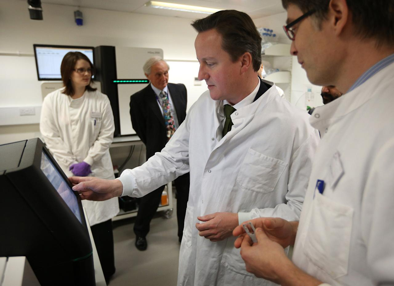 CAMBRIDGE, UNITED KINGDOM - DECEMBER 10:  Prime Minister David Cameron (2nd R) stands with Dr James Hadfield (R) as he uses a personal genome sequencing machine at the Cancer Research UK Cambridge Research Institute on December 10, 2012 in Cambridge, England. The government has announced GBP £100million of funding to enable 100,000 patients with cancer and rare diseases to have their entire genetic code sequenced.  (Photo by Peter Macdiarmid - WPA Pool/Getty Images)
