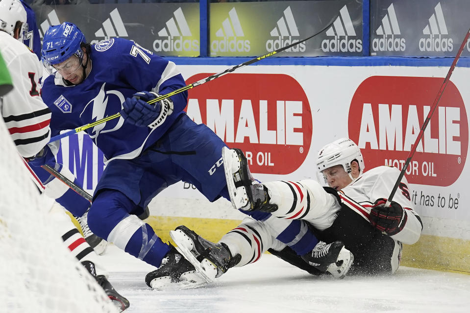 Tampa Bay Lightning center Anthony Cirelli (71) sends Chicago Blackhawks defenseman Connor Murphy (5) into the dasher with a check during the second period of an NHL hockey game Wednesday, Jan. 13, 2021, in Tampa, Fla. (AP Photo/Chris O'Meara)