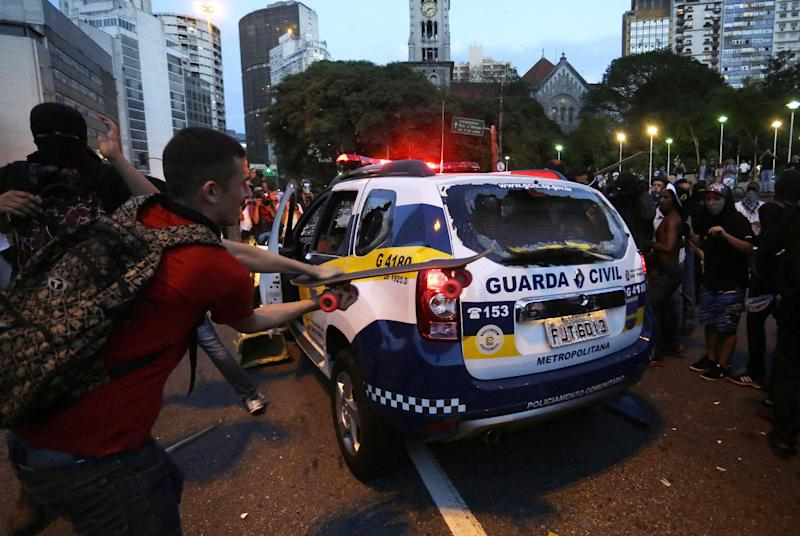 Demonstrators attack a municipal police car to protest the upcoming World Cup and demand better public services in Sao Paulo, Brazil, Saturday, Jan. 25, 2014. Last year, millions of people took to the streets across Brazil complaining of higher bus fares, poor public services and corruption while the country spends billions on the World Cup, which is scheduled to start in June. (AP Photo/Nelson Antoine)
