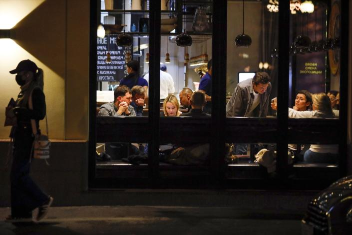 A woman wearing a face mask walks down a street as customers sit in a restaurant at Patriarshiye Prudy, a hip restaurant and bar district in Moscow, Russia, late Friday, Oct. 16, 2020. The outbreak in Russia this month is breaking the records set in the spring, when a lockdown to slow the spread was put in place. But, as governments across Europe move to reimpose restrictions to counter rising cases, authorities in Russia are resisting shutting down businesses again. (AP Photo/Alexander Zemlianichenko)