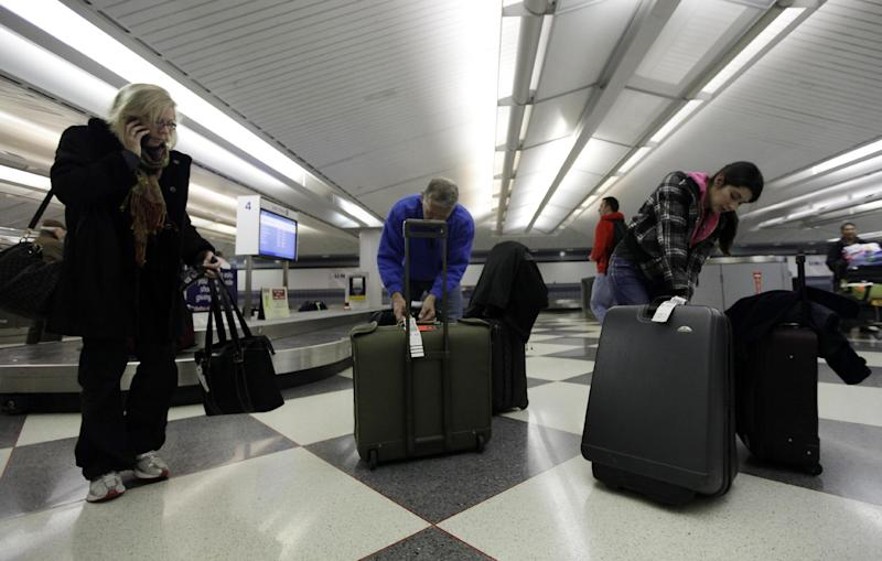 FILE - In this Dec. 22, 2011, file photo, travelers check their luggage at an United Airlines baggage claim area at O'Hare International Airport in Chicago. Airlines are slowly, steadily recovering from their meltdown five years ago, when, under the strain of near-record consumer travel demand, their performance tanked. Industry performance for all four measurements was slightly better in 2011 compared with 2010, according to the report being released Monday, April 2, 2012. (AP Photo/Nam Y. Huh, File)