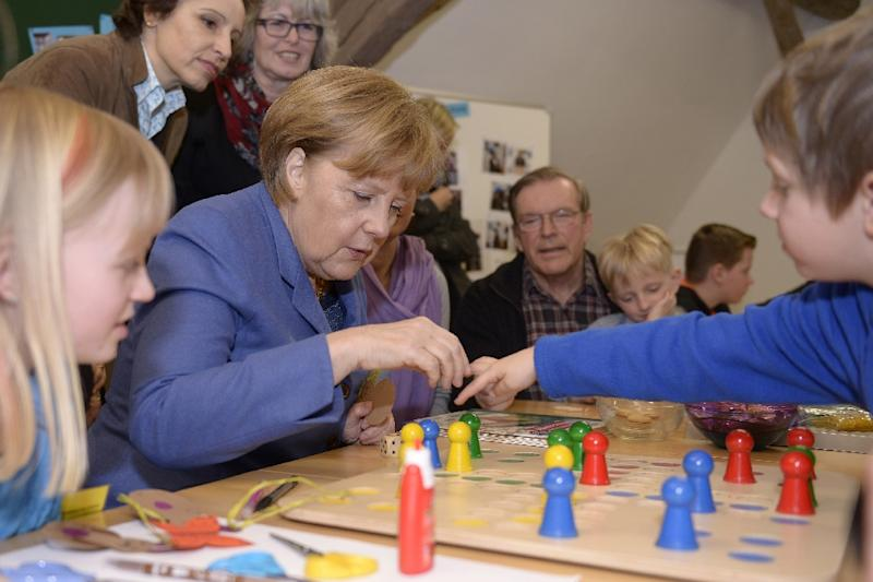 German Chancellor Angela Merkel plays with children on March 25, 2013 in Langenfeld, Germany (AFP Photo/Daniel Peter)
