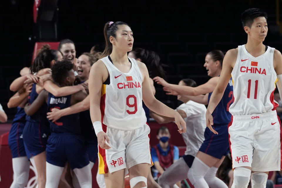 China's Meng Li (9) and Sijing Huang (11) walk off the court as Serbia celebrates their win following a women's basketball quarterfinal game at the 2020 Summer Olympics, Wednesday, Aug. 4, 2021, in Saitama, Japan. (AP Photo/Eric Gay)