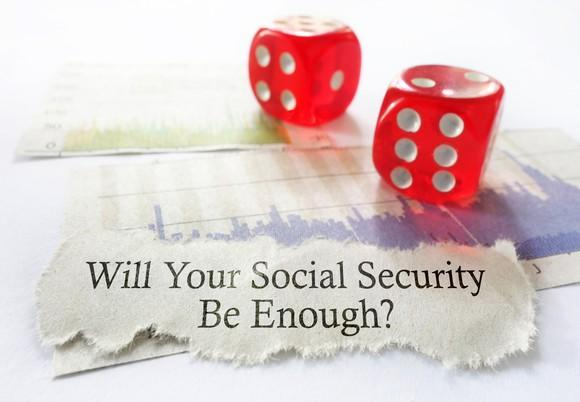 """two red dice over a torn piece of paper on which is printed, """"will your Social Security be enough?"""""""
